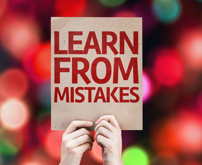 person holding up a card saying Learn From Mistakes